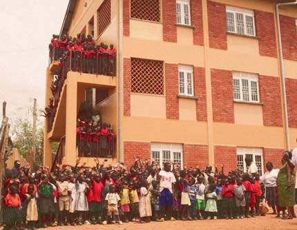 Excited students stand outside the new Meeting Point Kampala School building.