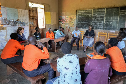 A group of Fellows, CEVs, and community leaders sit in a circle in discussion inside a classroom