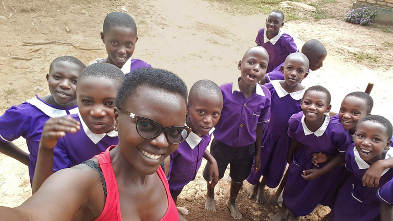Fellow Namata takes a selfie with a group of students