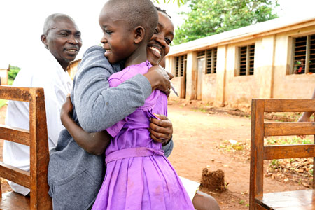 A Fellows gives a student a big hug and a smile