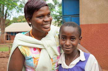 A Fellow laughs with an out-of-school child she brought back to school
