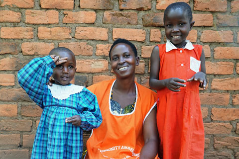 A CEV laughs with two students she helped enroll back in school