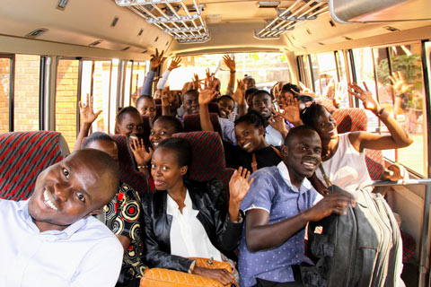 A group of Fellows is excited to ride the bus to a Building Tomorrow Primary School