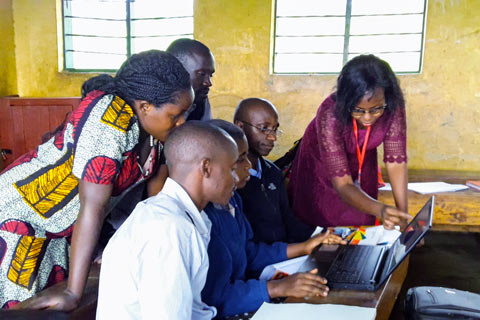 A Fellow teaches a group of community members how to use a laptop as they huddle around the screen
