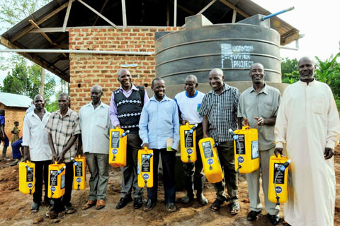 Community members hold specially designed yellow jerry cans in front of the water tank at their school