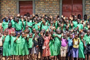 Dozens of students at the Building Tomorro Primary School of Kiryamusunku wave to the camera