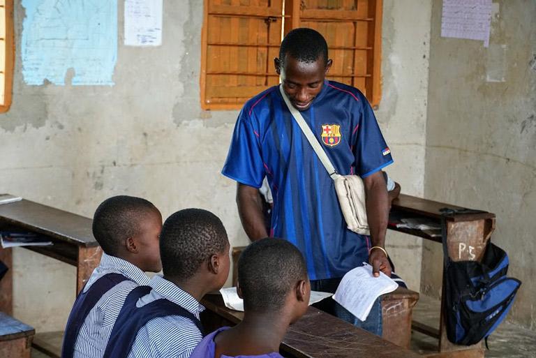 CEV Bashir helps students inside a classroom