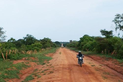 A Fellow rides a motorcycle down a rural dirt road