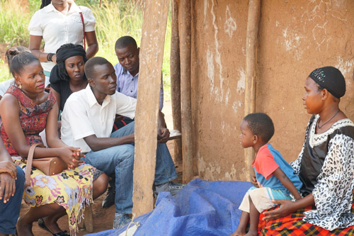 Fellows talk with a parent at her home as her child sits on her lap