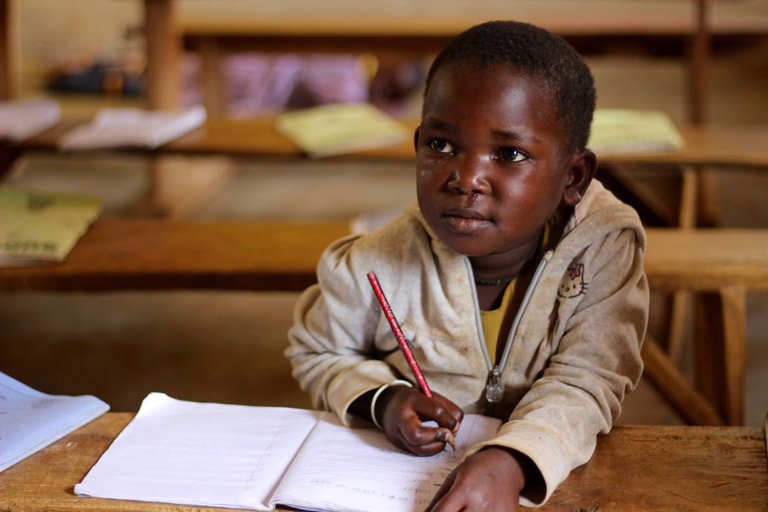 Robert takes pencil and paper notes at his desk as he surveys the front of the class