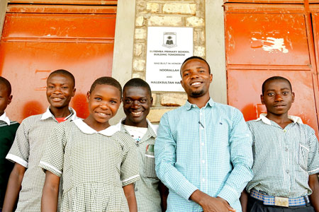 A Fellow poses with a group of students in front of the school's name plaque