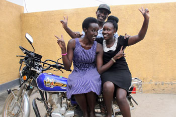A group of 3 Fellows pose on their motorcycle