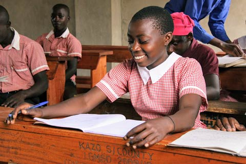 A Building Tomorrow student smiles while working at her desk