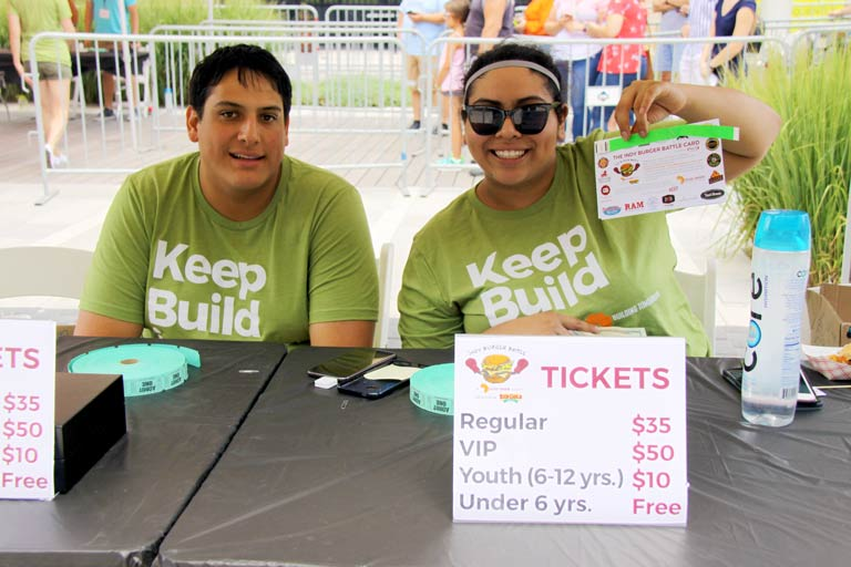 Two volunteers sell tickets at the Indy Burger Battle entrance