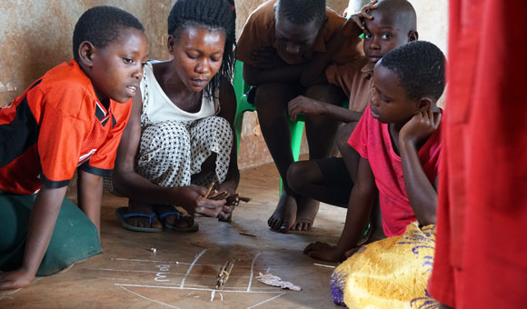 A Community Education Volunteers leads students in a math exercise involving bundled sticks