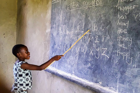 A student sounds out letters written on a chalkboard