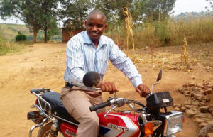 Enos, who started saving with the School Community Bank of the Building Tomorrow Primary School of Kabasegwa, has been able to borrow enough money to purchase a motorcycle to perform taxi rides and improve his income and pay for his child's school fees.