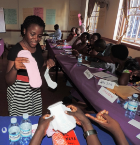 At a workshop for head teachers, Angella shows the differences between her reusable sanitary pad prototype and traditional non-reusable pads.