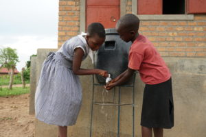 Girls at the BT Primary School of Bulyamushenyi wash their hands after playing an intense game of soccer.