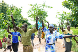 As guests arrive to break ground, community members emerge from their homes, singing and shaking branches of leaves—a symbol of peace and welcome.