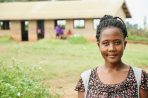 Building Tomorrow Fellow Lucky Natukunda stands in the compound of Mahani Primary School, one of the four schools at which she works.