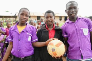 Congolese students Guard, Tantine, and Bahati (left to right) all participate in the Ball Project led by Fellow Lucky Natukunda at Mahani Primary School.