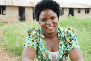 Community Education Volunteer Clementina Mutoni sits in front of Mahani Primary School.