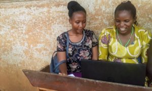 Fellow Lucky Natukunda helps Clementina learn basic computer skills during one of her 5P classes at Mahani Primary School